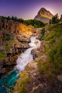 Swiftcurrent Falls at sunset with Grinnel Peak in the background in Glacier Nationalk Park Montana.