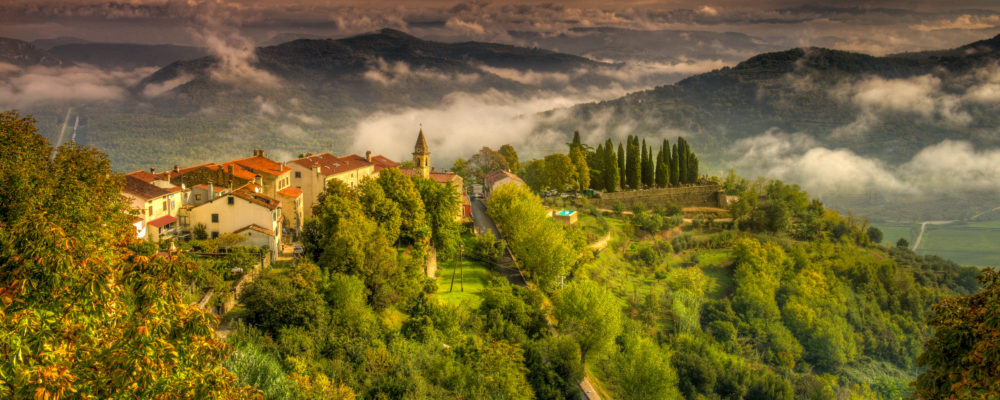 An eastward view from the Medieval city wall surrounding the Istrian village of Motovun, Croatia, to the Church of St. Margaret and the clouds beyond.